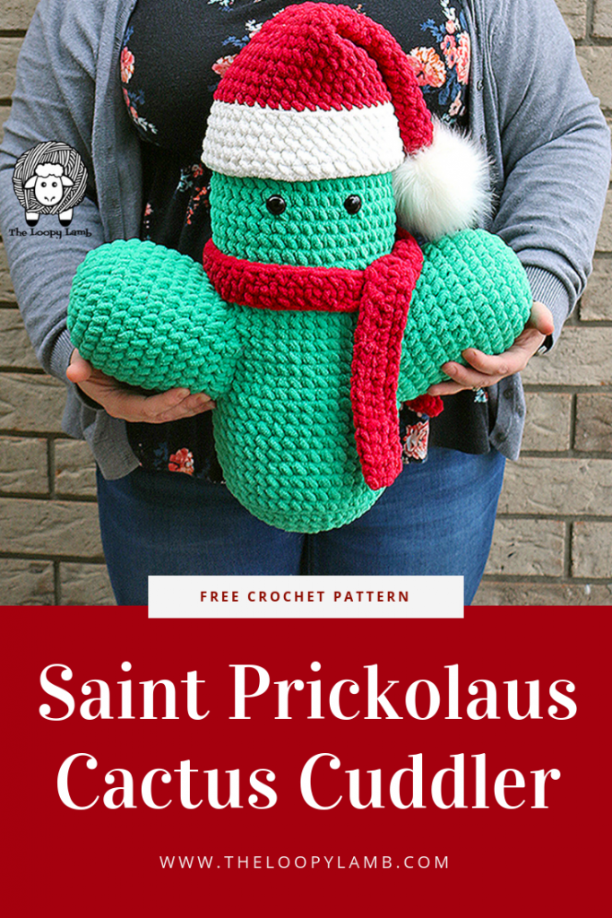 Giant amigurumi cactus cuddler toy wearing a scarf and santa hat being held in front of a woman