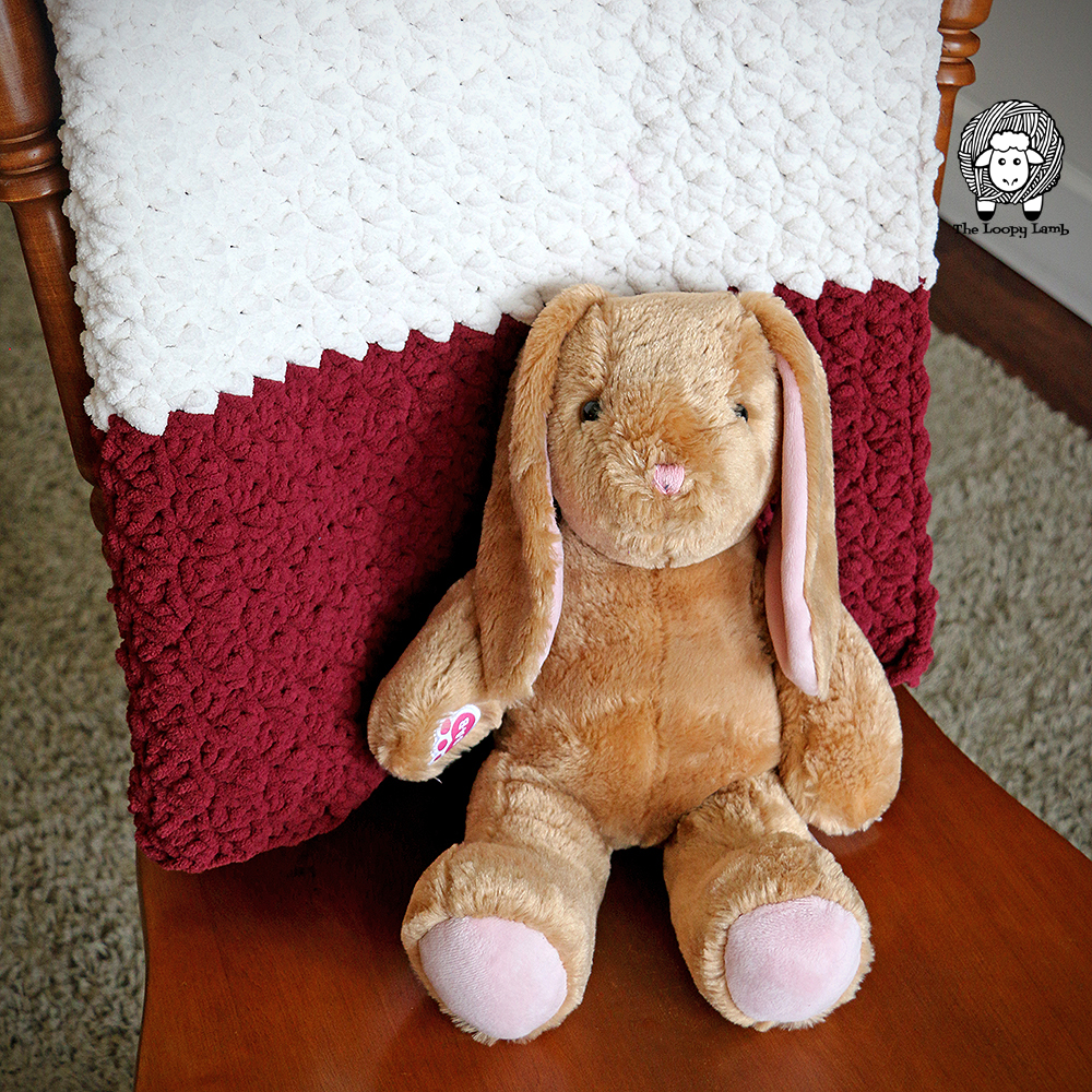 Stuffed bunny with Striped Thicket Stitch Blanket made with this easy crochet blanket pattern