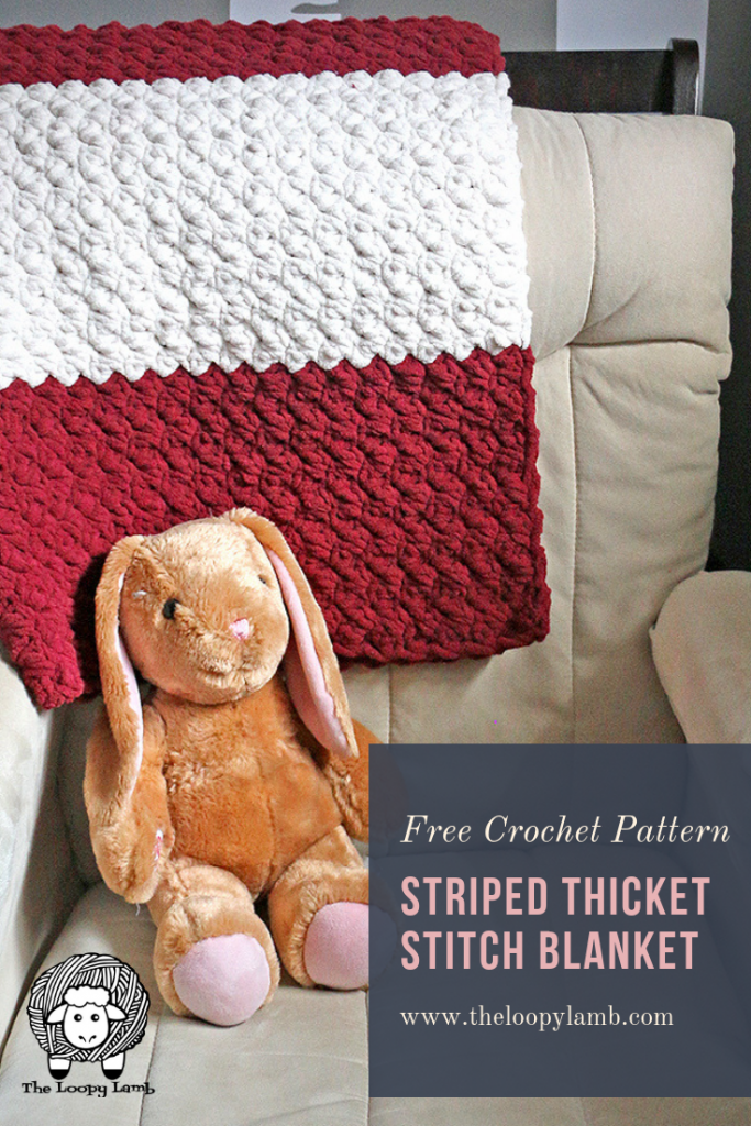 Striped Thicket stitch blanket draped over a rocking chair with a toy bunny in front