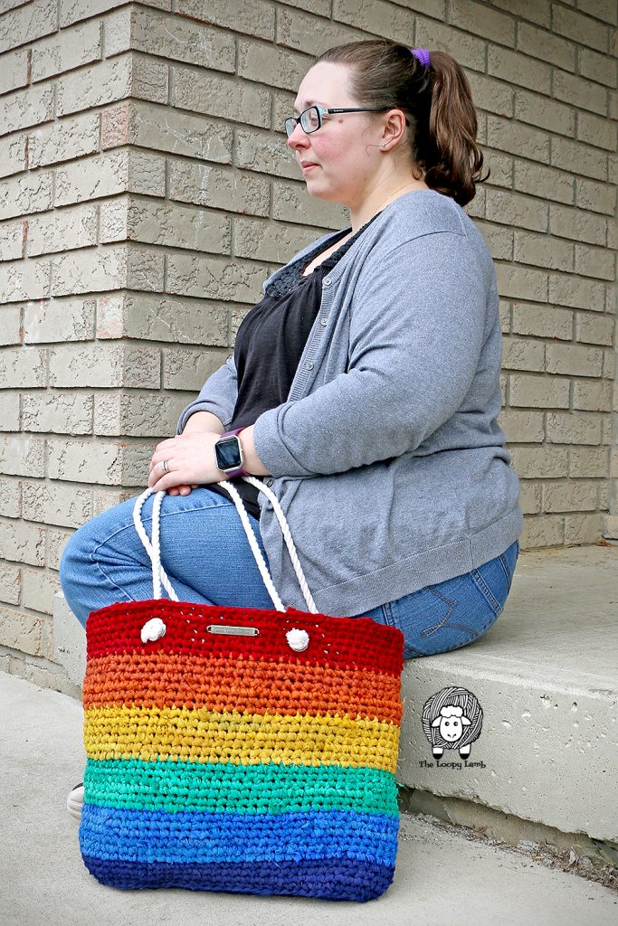 Girl sitting next to rainbow saver tote