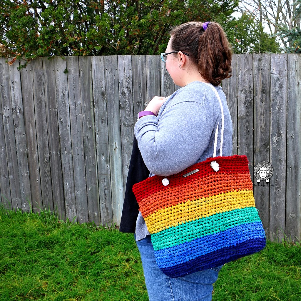 Girl holding rainbow saver tote