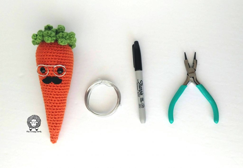 Crochet Carrot named Carter lined up next to tools used in this pattern
