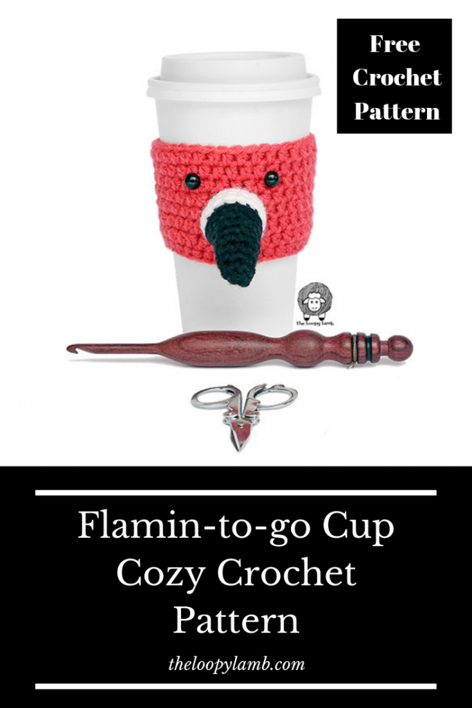 Crochet Cup Cozy that looks like a flamingo on a white cup with a crochet hook and scissors laying in front of it.