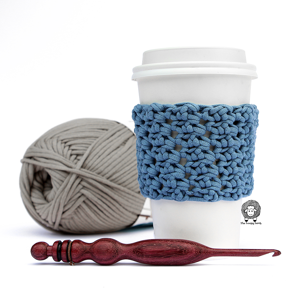 The Elgin Cup Cozy pictured with a beautifully handmade wooden crochet hook and a skein of Bernat Maker Home Dec yarn.