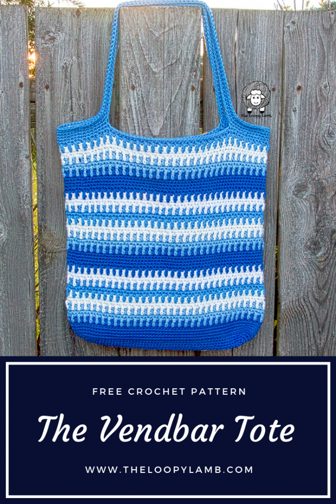 The Vendbar Tote Bag hanging on a fence, comprised of stripes of blue and white.