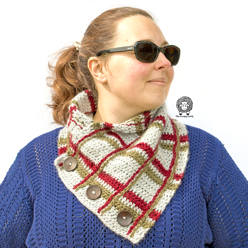 Girl wearing the Crochet Plaid Cowl, made in grey, red and green.
