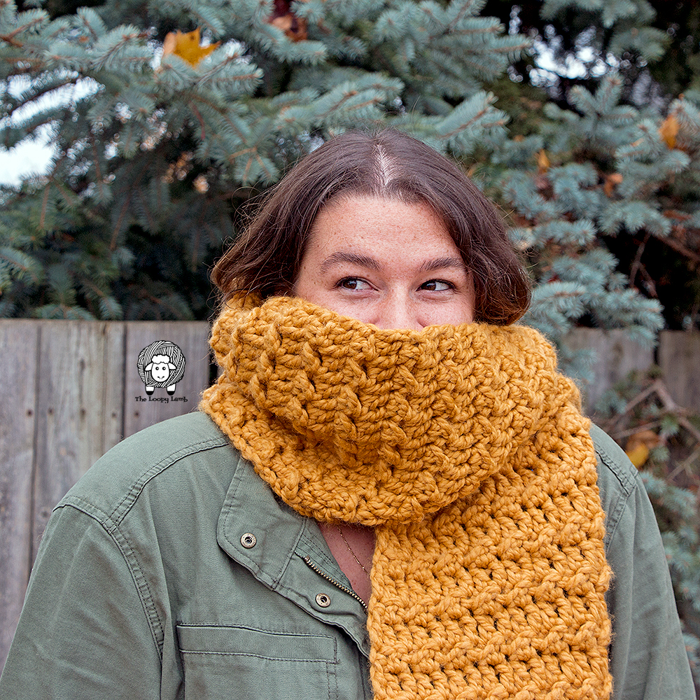 Woman with face partially concealed by scarf made with this free crochet scarf pattern.