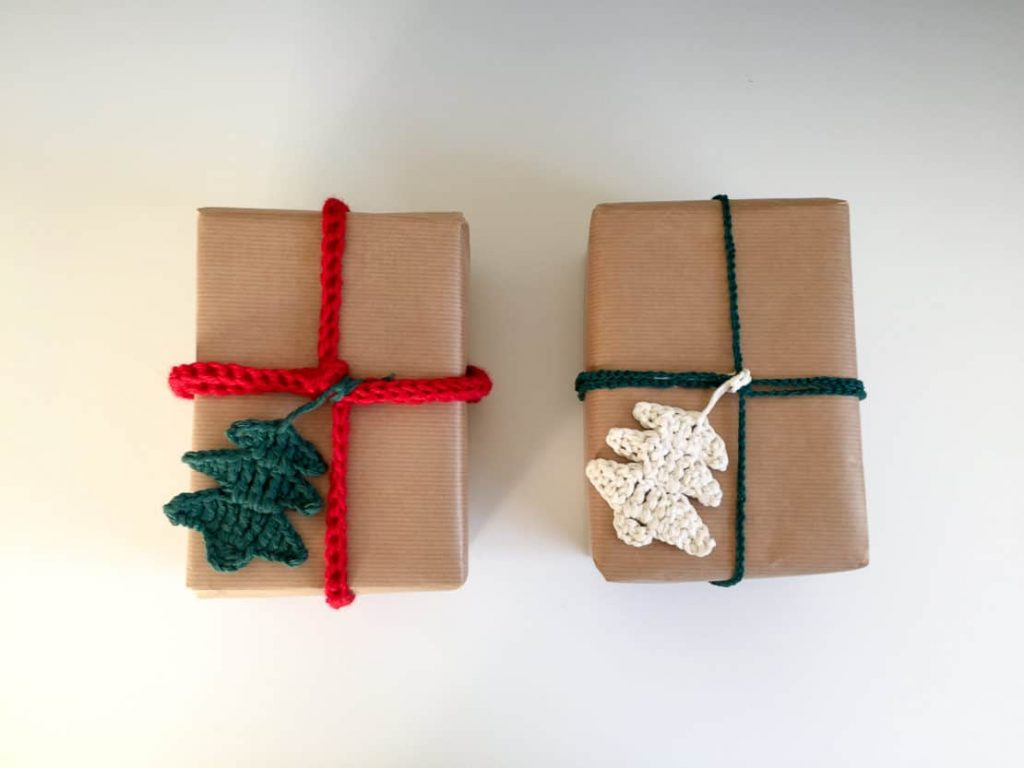 two packages wrapped in brown paper with yarn decorations