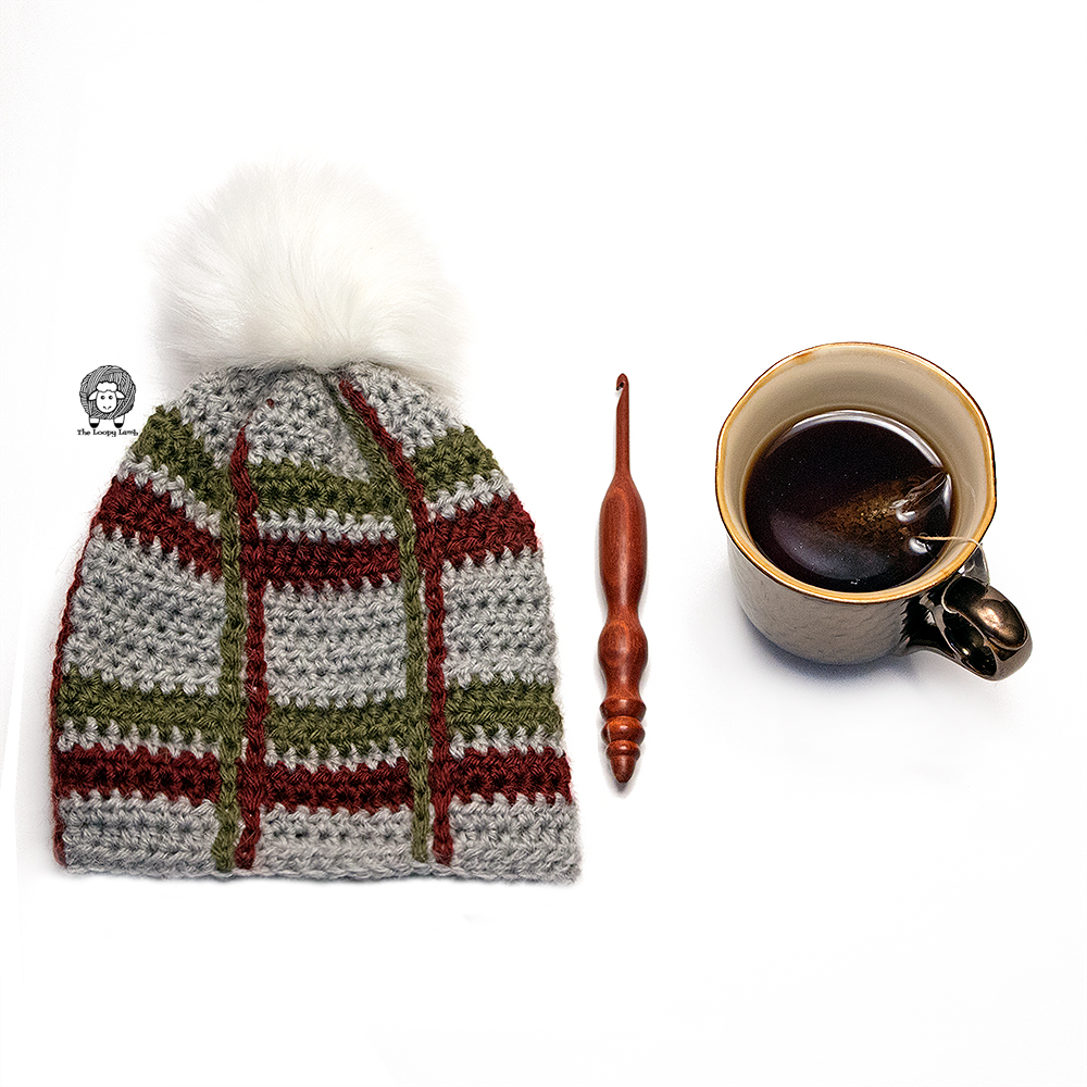 Crochet Tartan Beanie folded and lain flat, next to a wooden crochet hook and a coffee.
