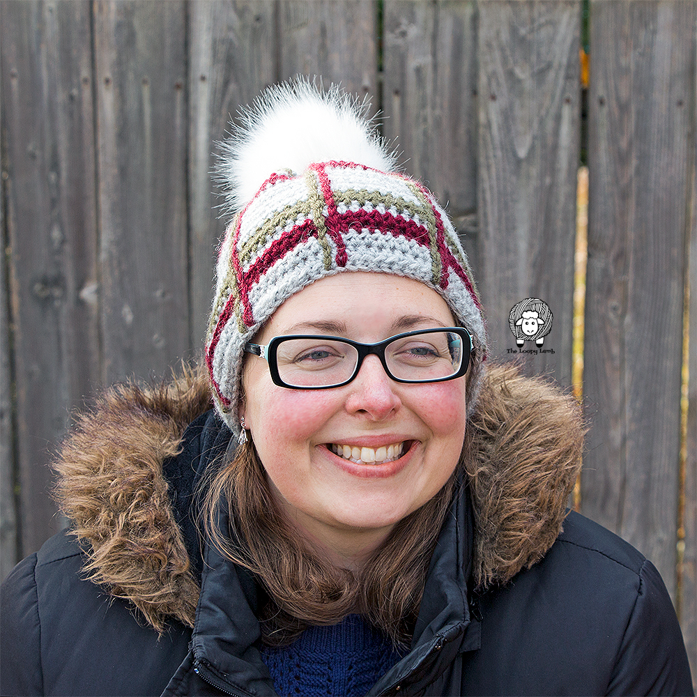 Woman smiling wearing the crochet tartan beanie