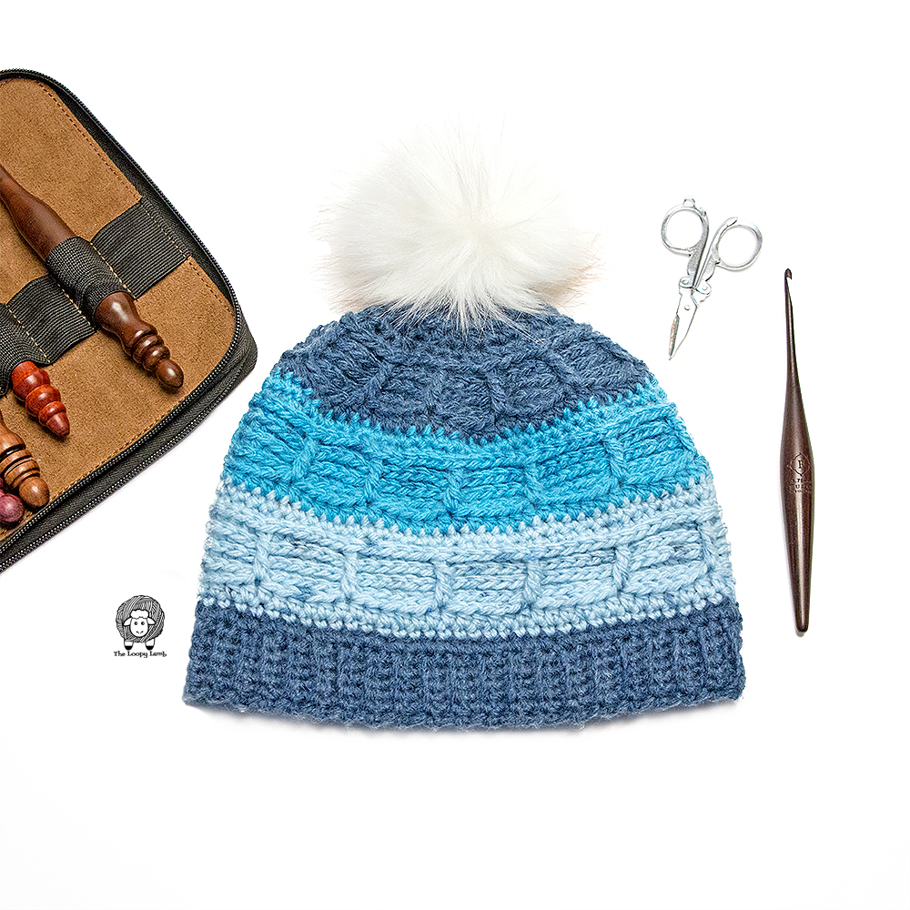 Juneau Blues Beanie (made with this free crochet hat pattern), laid flat next to a crochet hook and scissors.