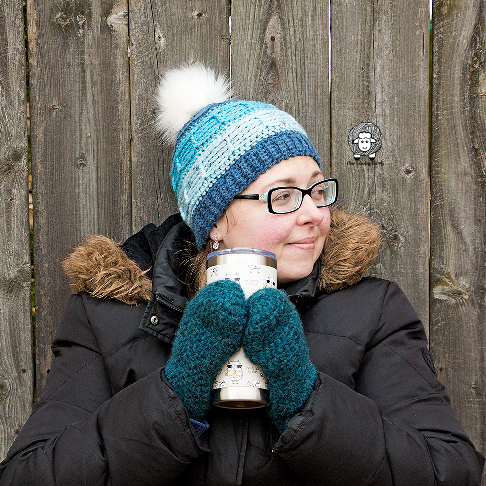Woman wearing beanie made with this free crochet pattern, holding a mug.
