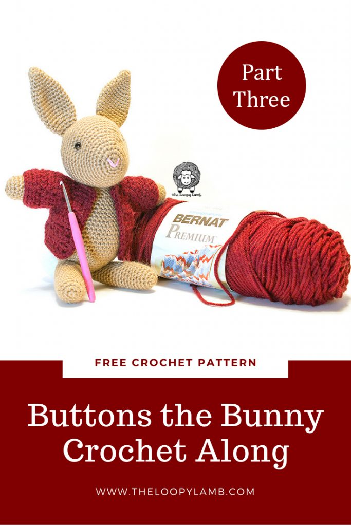 Buttons the Bunny sitting next to a skein of Bernat Premium yarn which is used in this free bunny crochet along pattern.