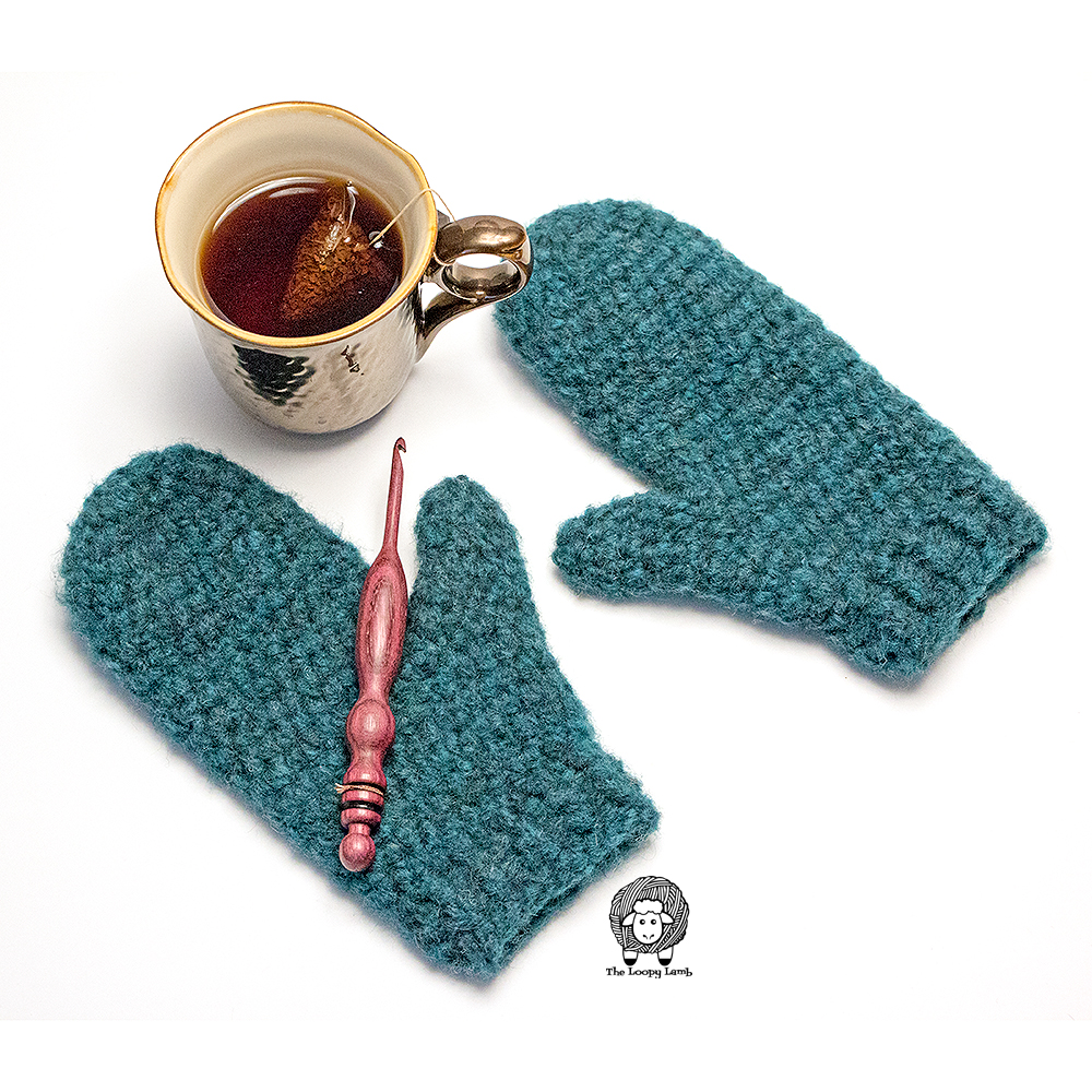 Mittens made with this free crochet mitten pattern, layed flat on either side of a mug filled with tea.