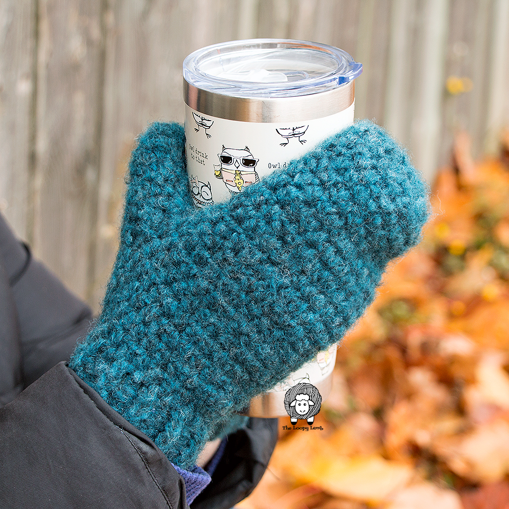 Up close view of the Norse Crochet Mittens being worn and holding a mug.