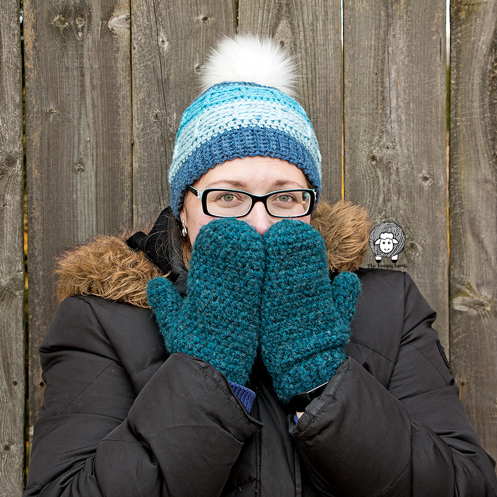 Woman covering lower part of face with newly crocheted mittens.