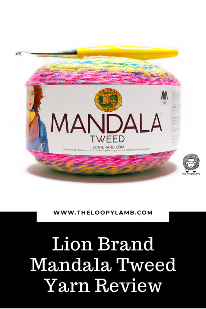 Lion Brand Manadala Tweed Yarn Cake a yellow Furls Crochet Hook laying on top of it.