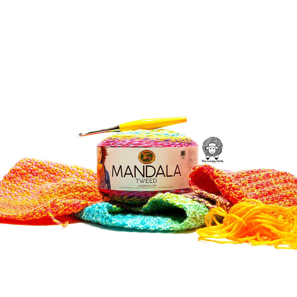 Image of Lion Brand Mandala Tweed Yarn cake amongst a crochet project with a furls crochet hook on top.
