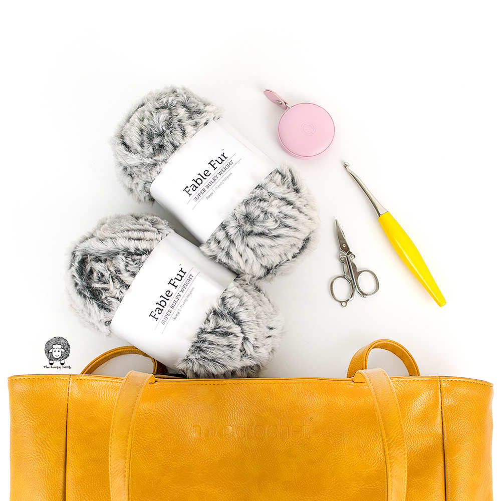Fable Fur Yarn and crochet accessories coming out of a mustard tote from Wecrochet.com