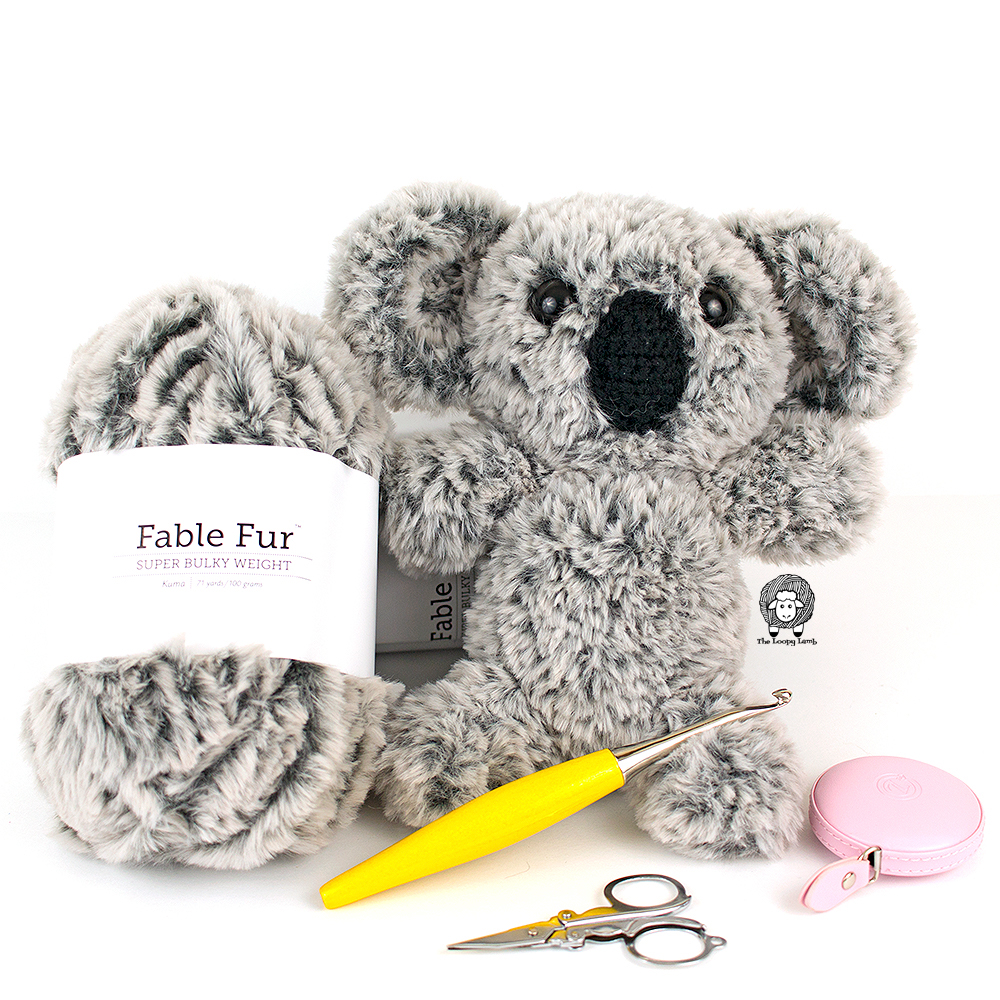Crochet Koala next to a ball of fable fur yarn and some crochet accessories