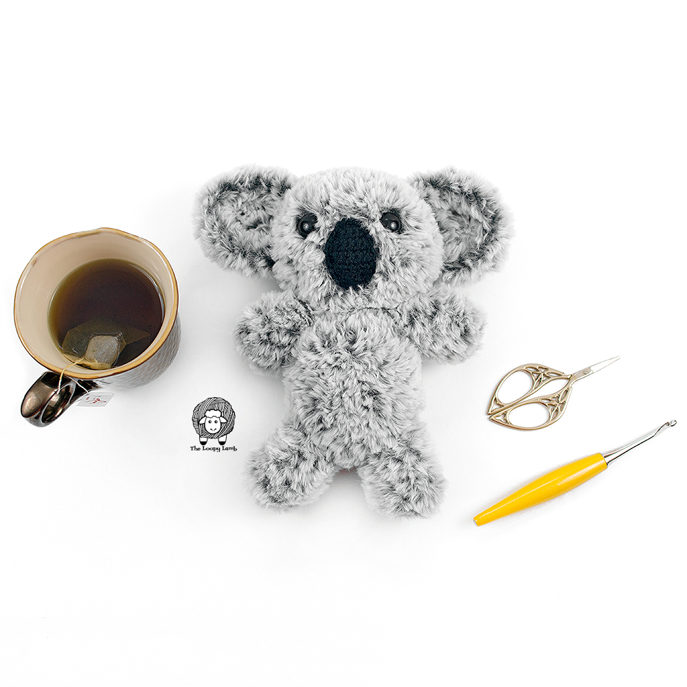 Crochet Koala next to a tea, scissors and a yellow furls crochet hook