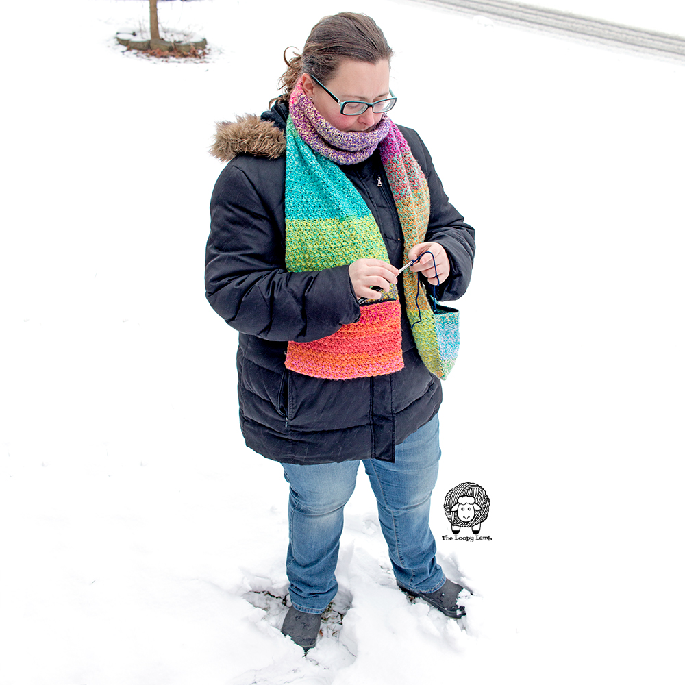 Woman wearing a crochet scarf and crocheting with tools stored in the pockets.