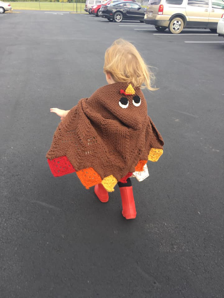 Child wearing a turkey themed poncho