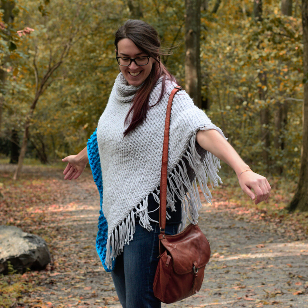 Woman wearing a fringed poncho with her arms out wide.
