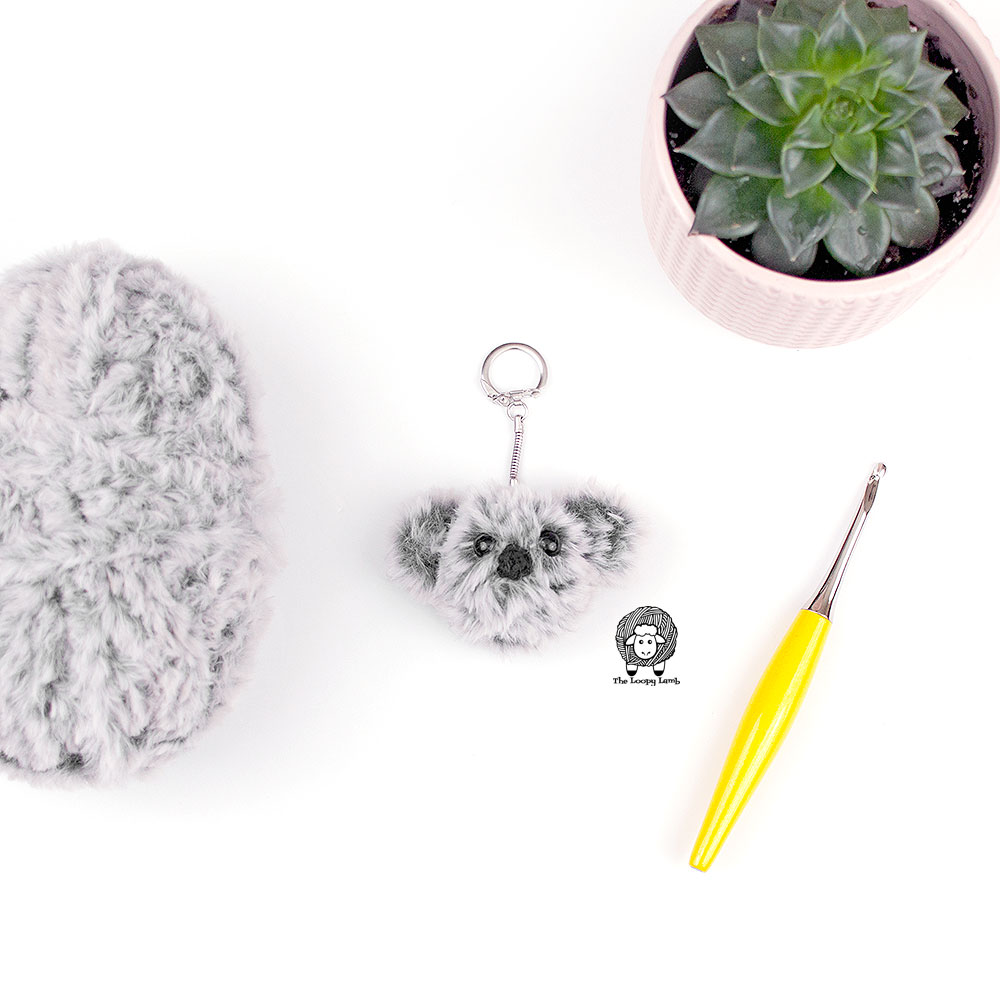 Crochet Koala Keychain made with faux fur yarn next to a yellow furls crochet hook and a cactus plant.