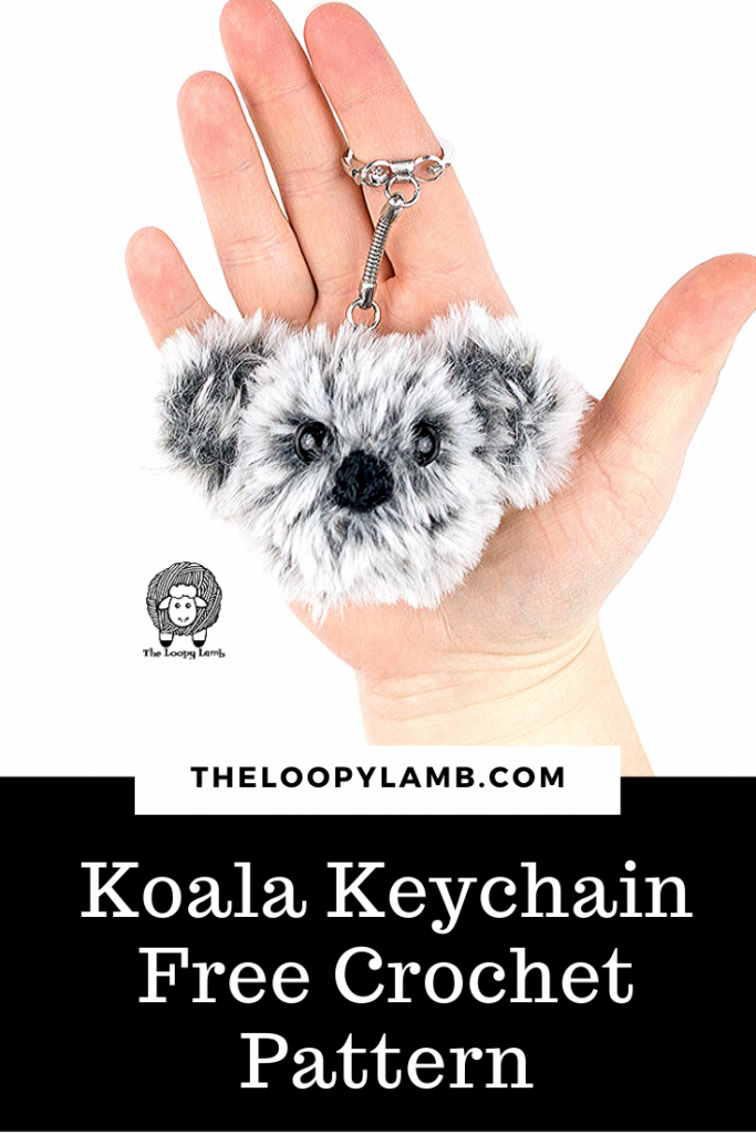 Crochet koala keychain made with faux fur yarn being held in an open hand.