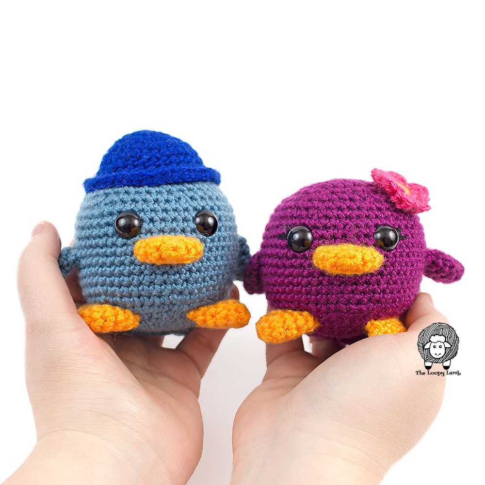 Two amigurumi birds being held i someone's hands.