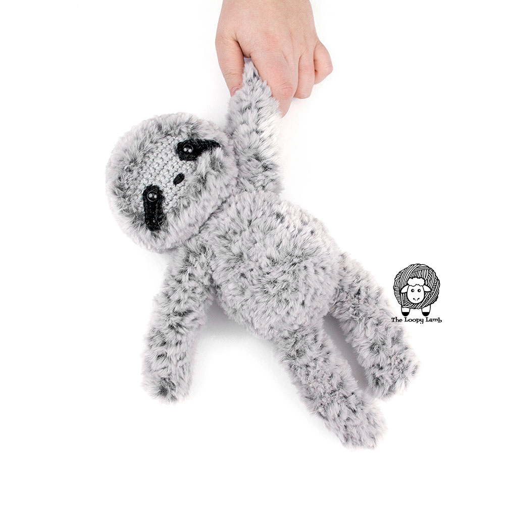Crochet sloth being held by the hand.