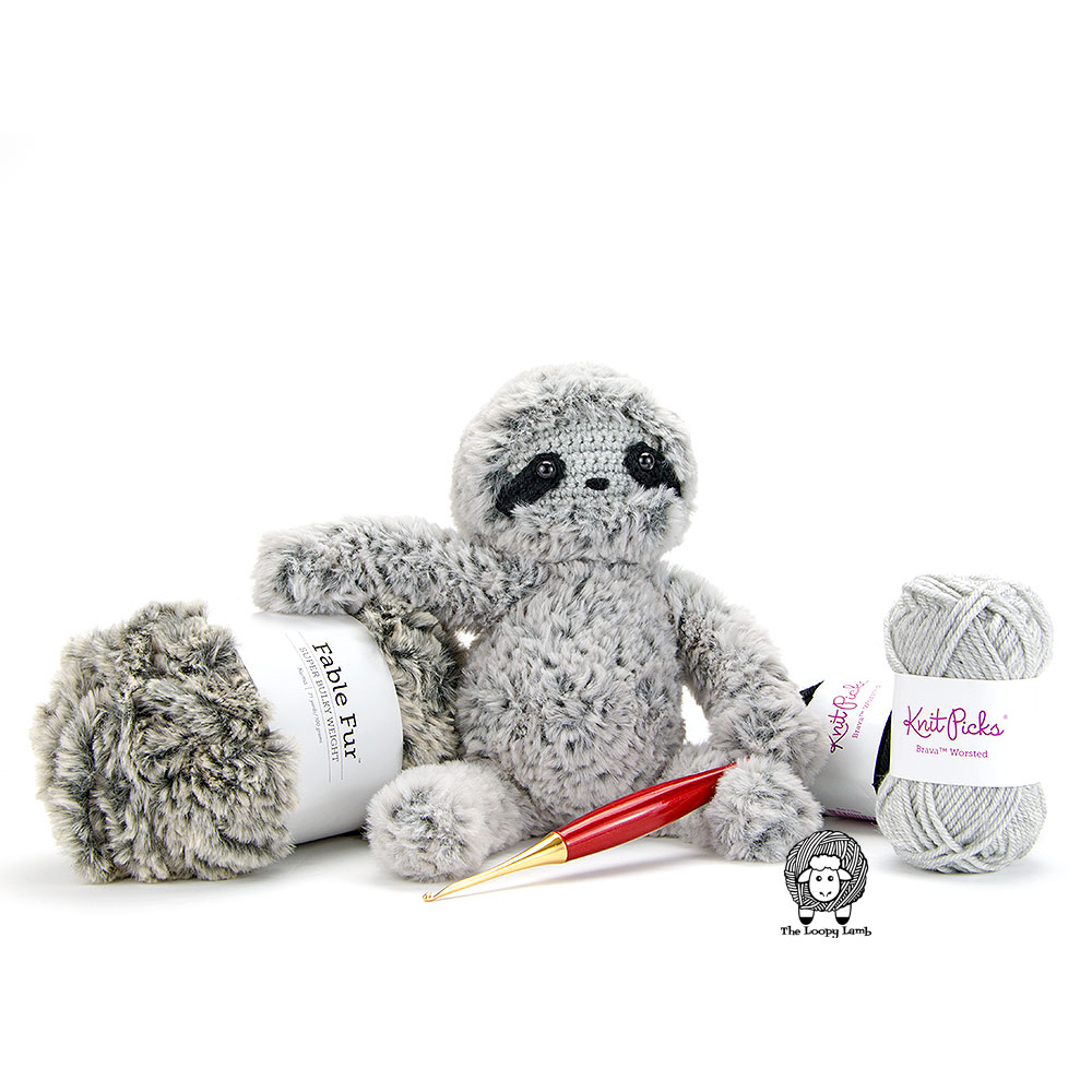 Crochet sloth resting it's arm on a ball of faux fur yarn with a crochet hook in it's lap.
