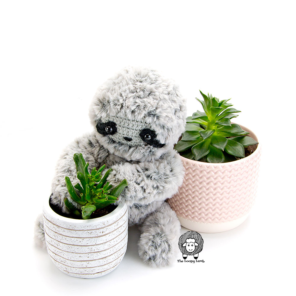 Crochet sloth looking at a plant.