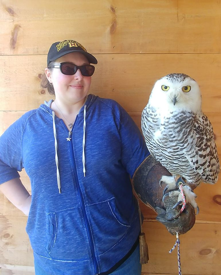 Picture of a woman holding a snowy owl on her arm.