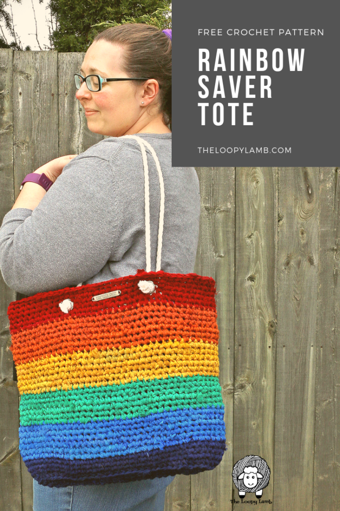 woman looking over her shoulder, wearing a rainbow crochet tote bag made with this free crochet tote bag pattern.