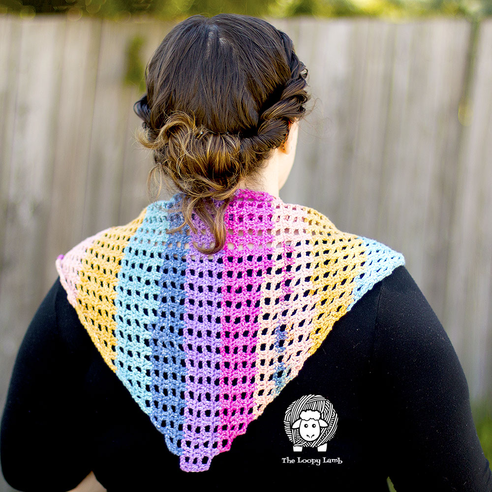Woman wearing a colourful one skein shawlette on her shoulders
