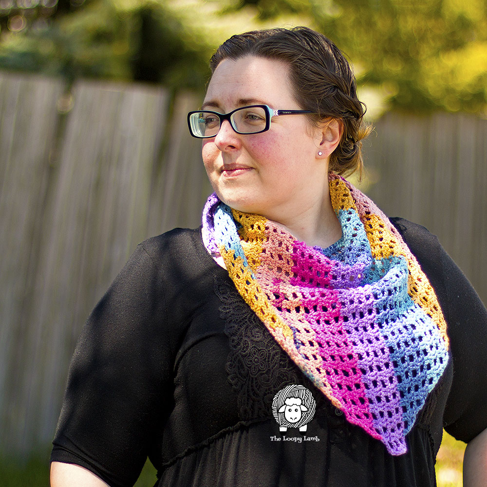 Woman looking off into the distance wearing a colourful shawlette made with this free crochet pattern