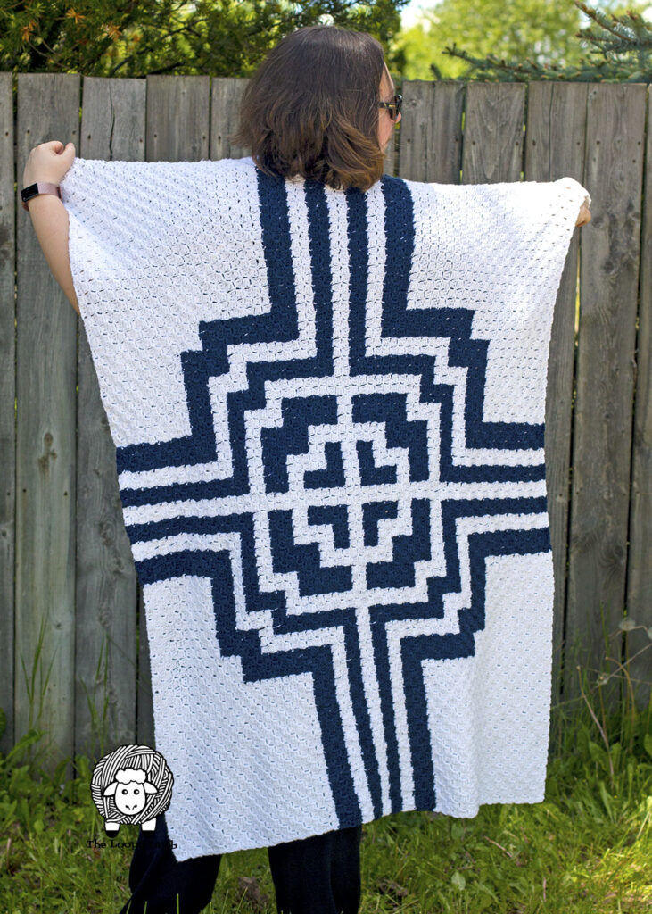 Woman holding a navy blue and white C2C blanket across her shoulders