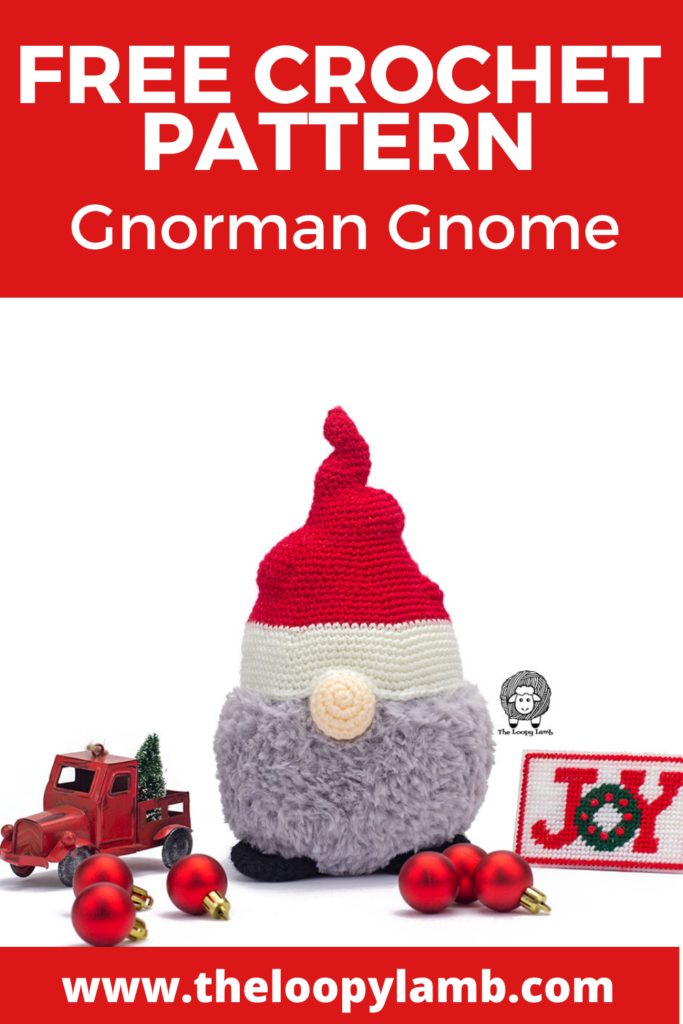 crochet christmas gnome wearing a knobbly red hat surrounded by Christmas decorations