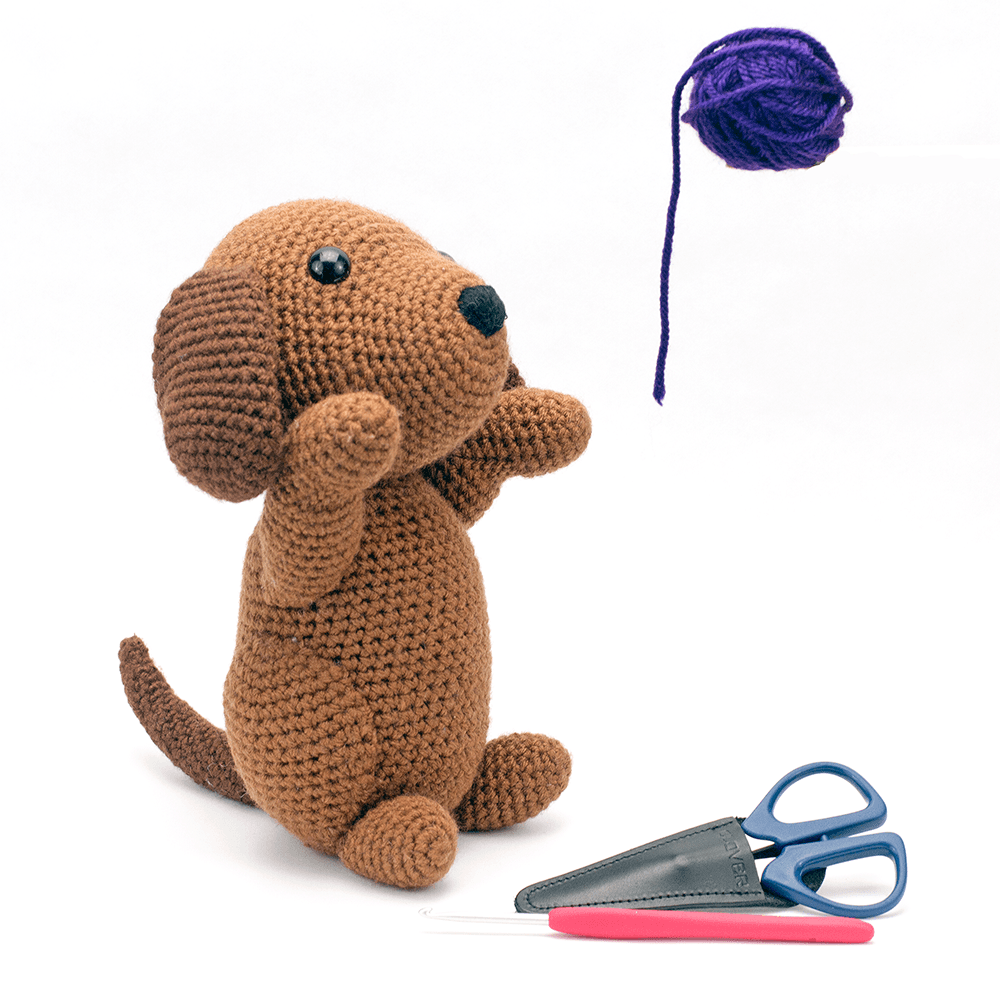 Amigurumi dog with some Clover USA Crochet tools looking up at a ball of purple yarn.