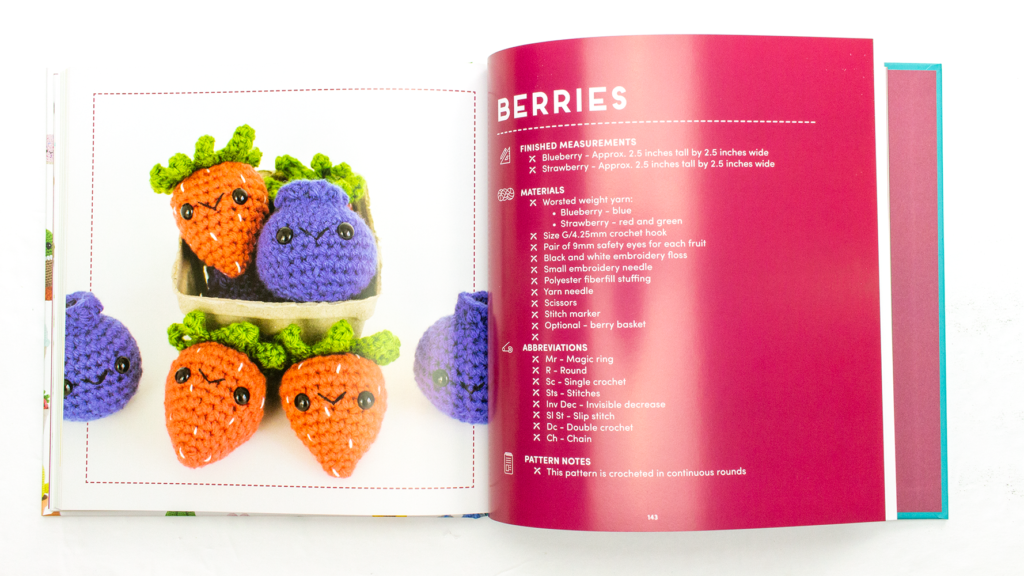 Crochet strawberries and blueberries inside the amigurumi book being reviewed
