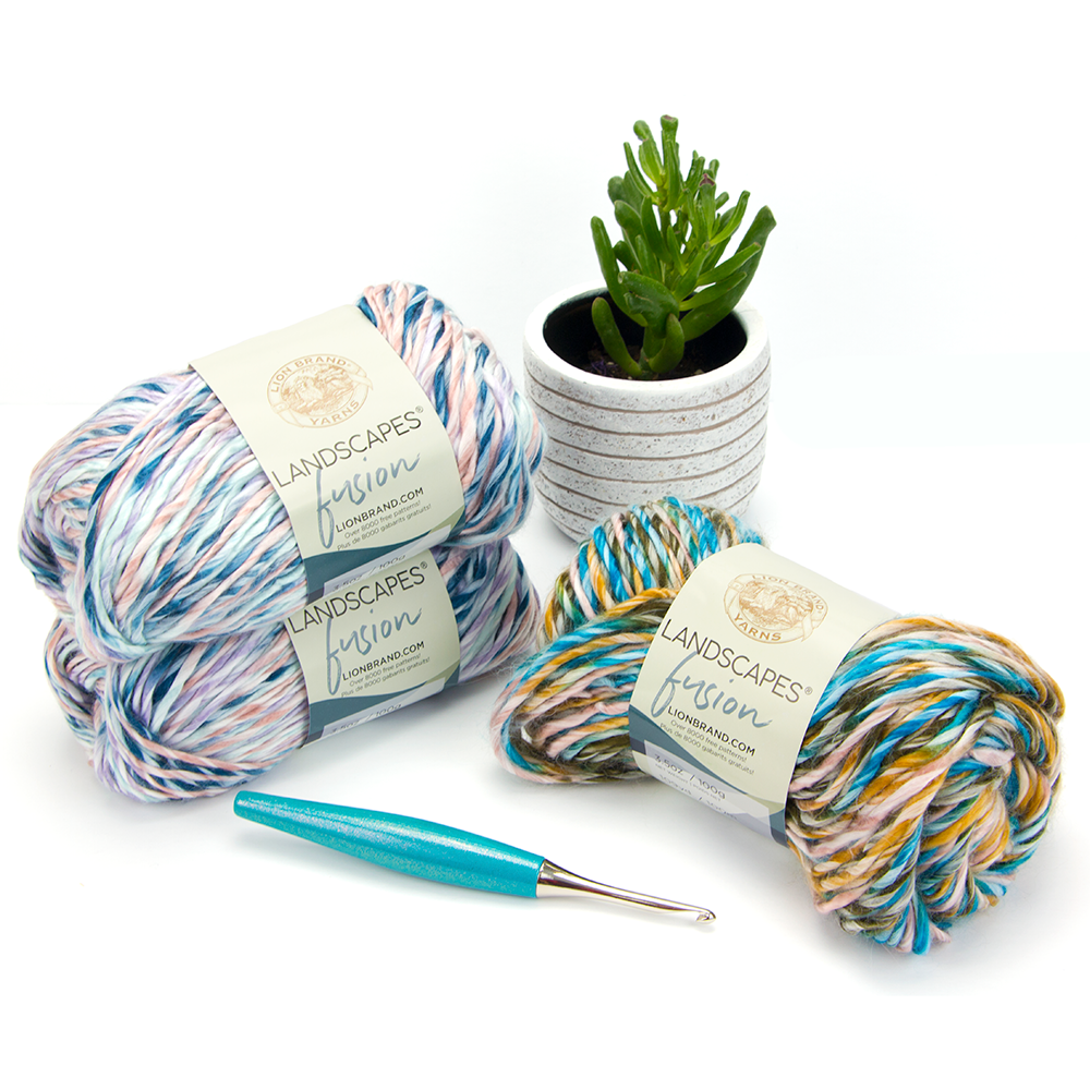 Three skeins of the new Landscapes yarn from Lion Brand and a teal Furls Crochet Hook