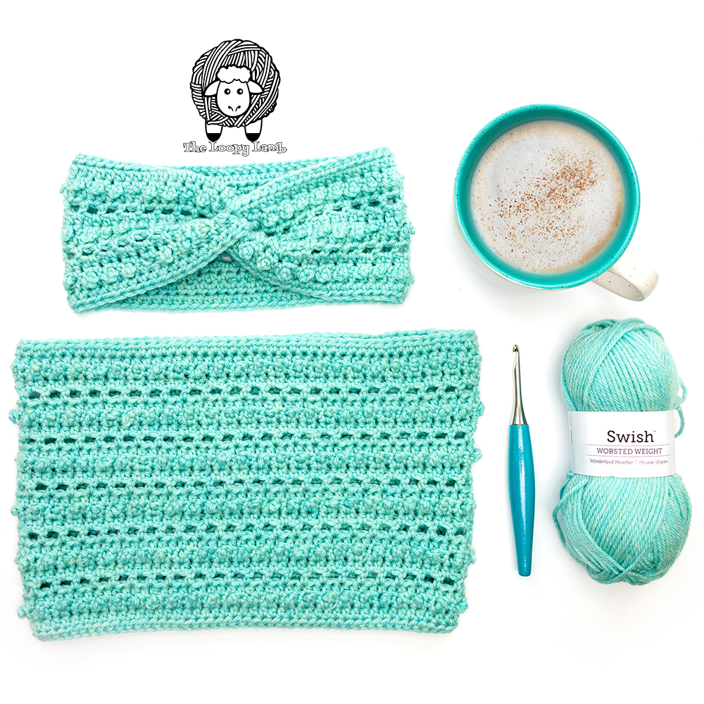Crochet earwarmer and cowl set lain out in a flat lay with coffee, yarn and a furls crochet hook