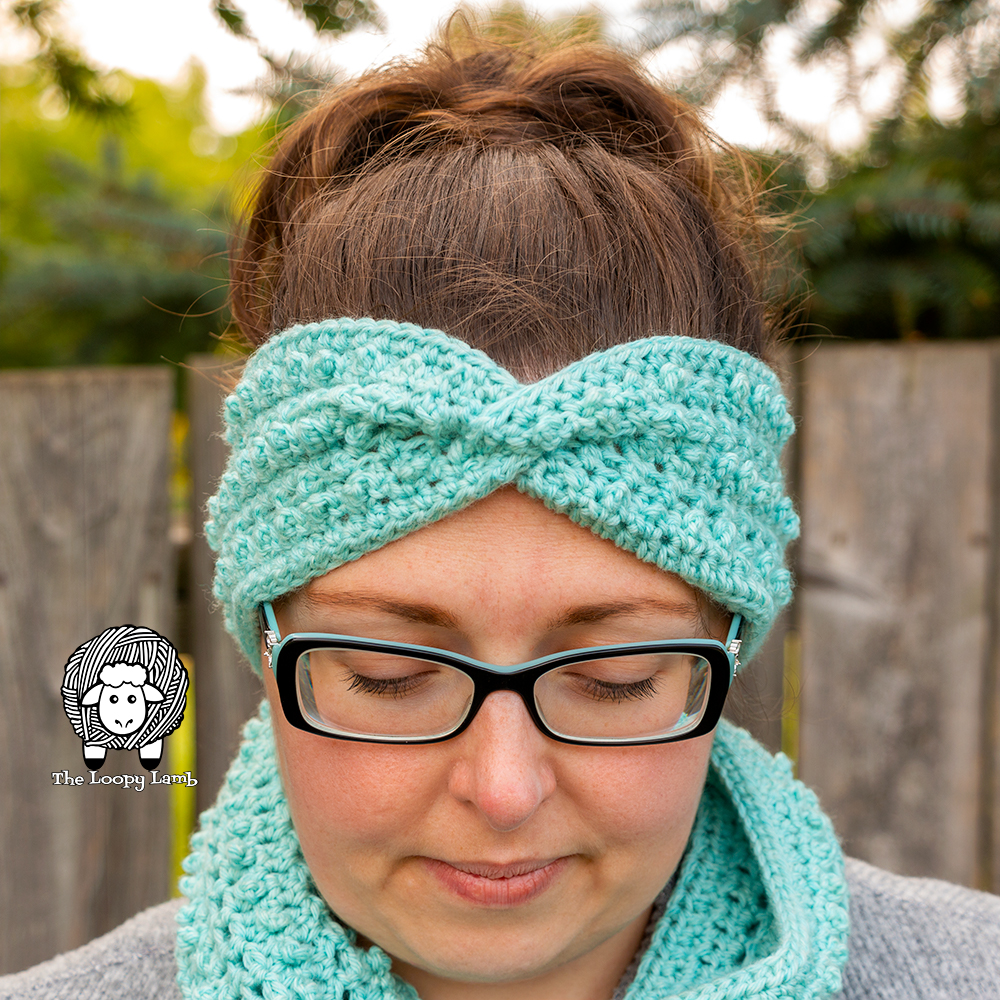 Woman looking down wearing a crochet ear warmer and cowl set