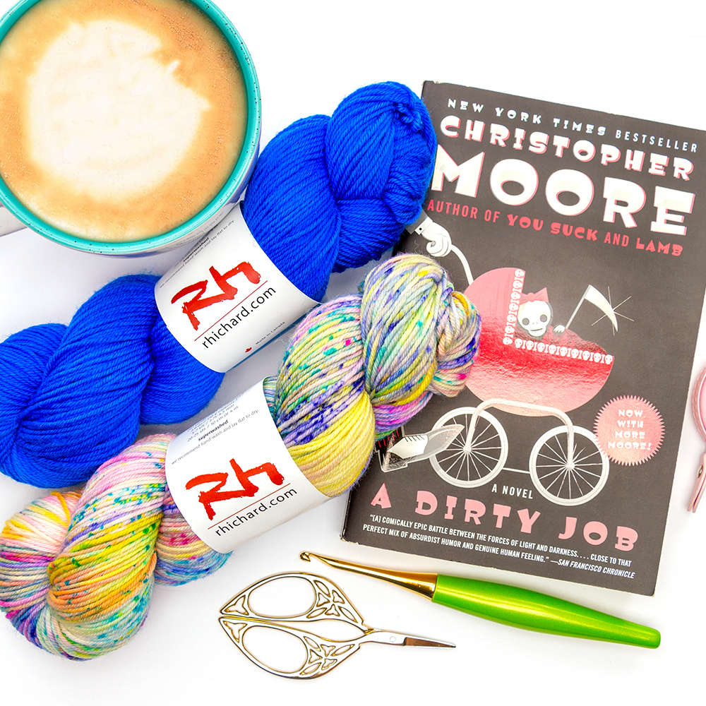 Two hanks of sirocco yarn from Rhichard Devrieze yarns on top of a book with a coffee and some crochet accessories.