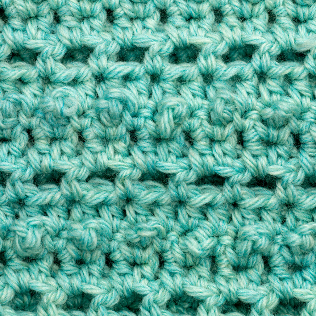 Close up image of the stitch definition in a crochet swatch using this yarn