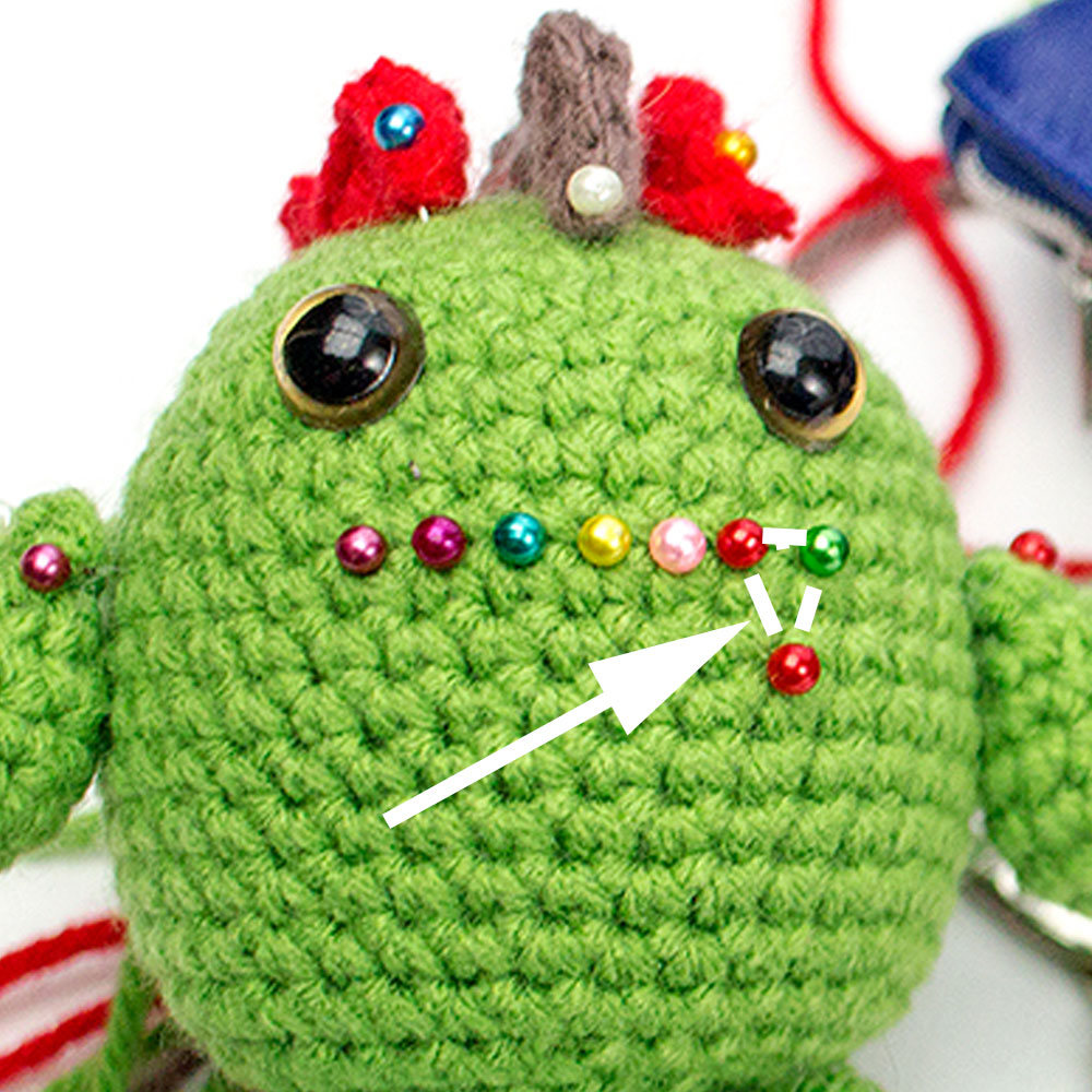 Pins placed on an amigurumi toy showing where to embroider