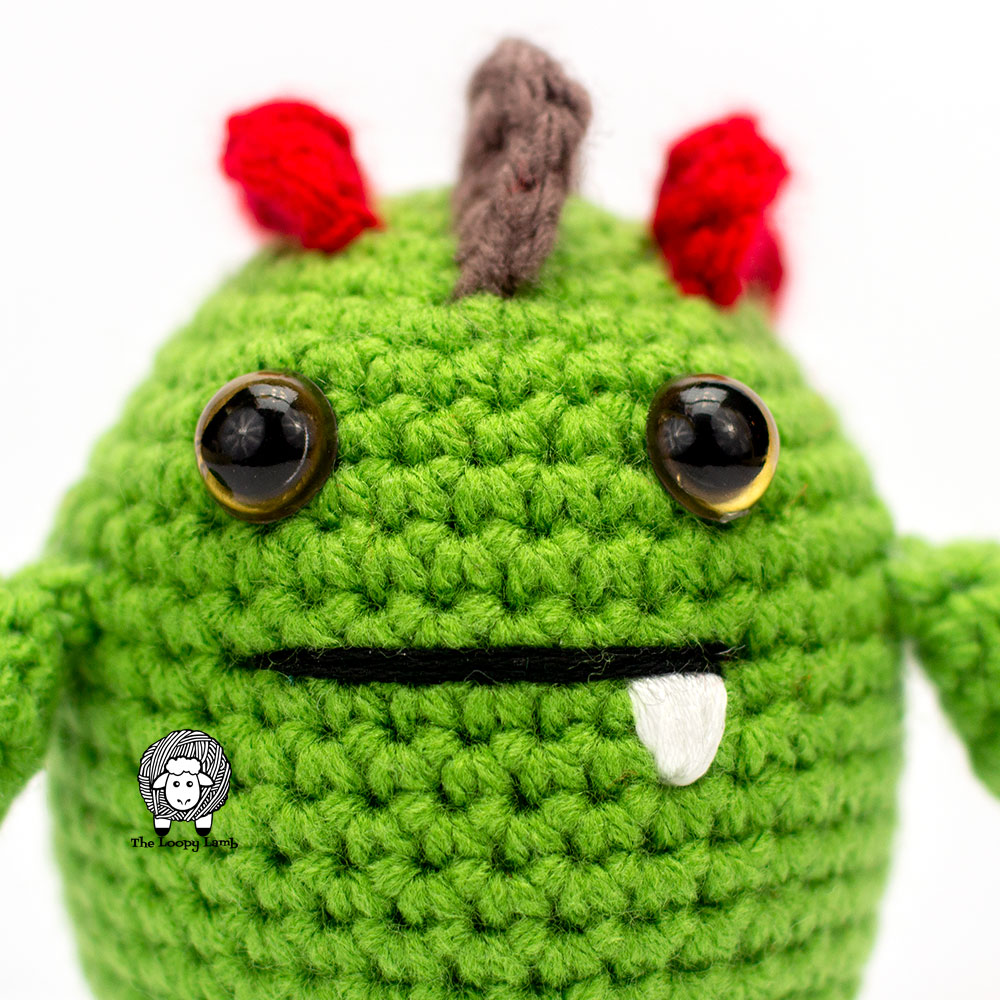 Close up of an amigurumi crochet monster's face