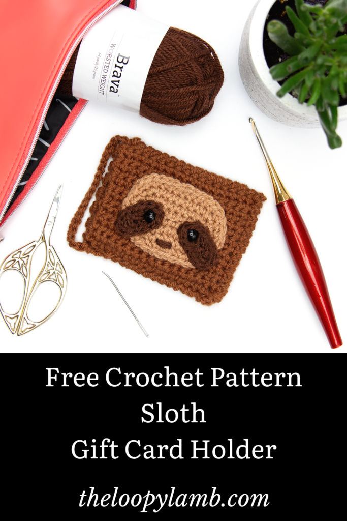Crochet gift card holder with a sloth face on it in a flat lay